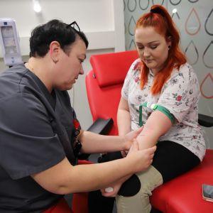 sairaanhoitaja etsii verisuonta nuoren naisen kyynärtaipeesta