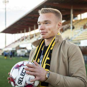 Ilmari Niskanen seisoo jalkapallo käsivarsilla Savo Areenan kentällä.