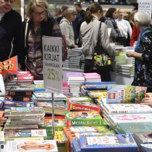 Barn bläddrar i barnbok framför bord med massor böcker.