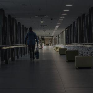 En man går i en mörk sjukhuskorridor.