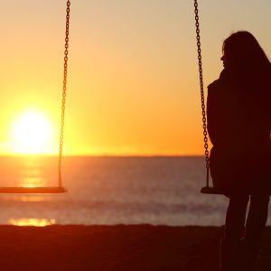 Kvinna sitter på gunga i solnedgång, bredvid henne en tom gunga