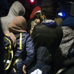 Joukko siirtolaisia. Keskellä pieni lapsi.