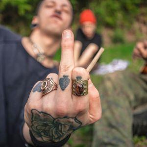 Keskisormea näyttävä tatuoitu käsi, taustalla epäselvästi henkilöitä ja kitara.