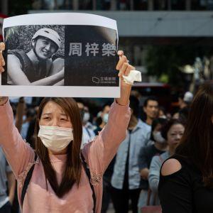 Nuori nainen kannattelee tulostetta, jossa näkyy perjantaina kuolleen opiskelijan kuva.
