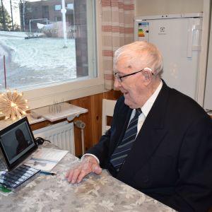 Eino Nurminen puhuu tablettilaitteen avulla hoitajan kanssa.