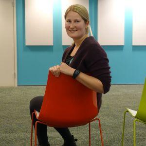 Foto på Katarina Rehnström som sitter på en färgrann stol i EHYTs kontor