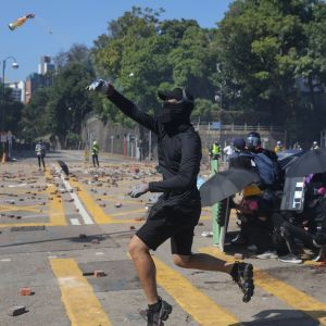 Naamioitunut mielenosoittaja heittää polttopullon.