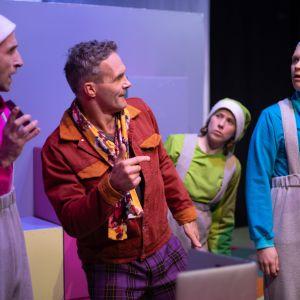 Tre skådespelare i pastellfärgade tomtekläder tittar förvånat på en fjärde man i ljusbrun skinnrock mellan dem.