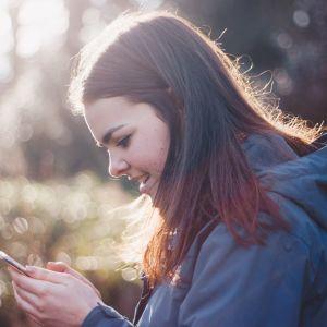 Tyttö katsoo kännykkää.