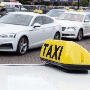 Två taxibilar och en taxiskylt.