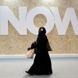 """En svartkädd kvinna går förbi en stor banderoll med texten """"NU"""" under FN:s klimatmöte i Madrid"""