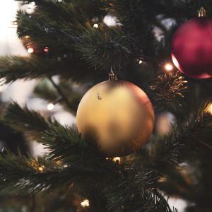 Julgran med julgransbollar i rött och guld.