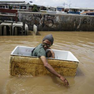 Jakartan asukas liikkui veden valtaamassa kaupungissa styroksilaatikon avulla.