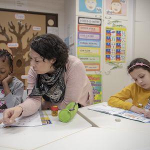 Opettaja neuvoo oppilasta tunnilla