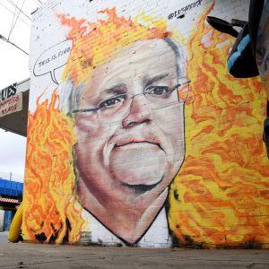 Australiens premiärminister Scott Morrison på en affisch i Melbourne 7.1.2020. Morrisons och regeringens hantering av skogsbrandskrisen och bristande engagemang i utsläppsfrågor kritiseras hårt