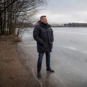 Harri Gustafsberg seisoo jäätyneen Tohlopinjärven rannalla