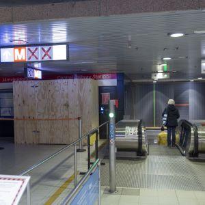 Punaisella ruksilla merkityt pyörätuoli- ja hissiopasteet sekä työmaa-alueen lautaseinä Helsingin päärautatieaseman metroasemalla.