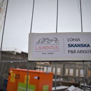 Skylt med texten Laurentiustalo -huset på byggarbetsplats.