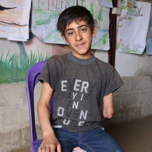 Syriska Amir sitter på en stol framför en vägg med barnteckningar. Hans armstump syns.
