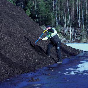 Man gräver jord från stor hög.