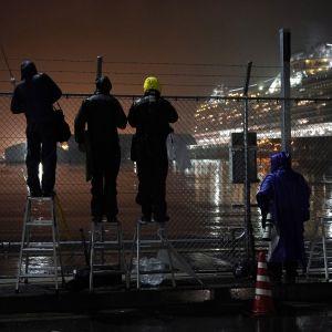 Journalister följer med på avstånd hur passagerare på Diamond Princess fick stiga i land i Yokohama.
