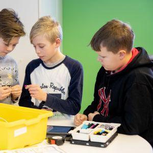 Lietsalan koulun viidesluokkalaiset Niclas Noko, Lauri Luoto ja Konsta Evesti kasaavat koodattavaa robottia.