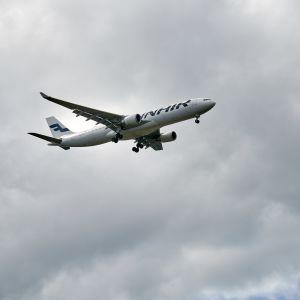 Finnairs flygplan flyger i en grå och molnig himmel.