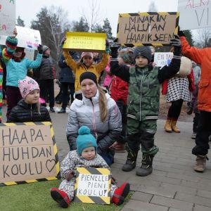 Äiti ja lapset puolustavat kyltein koulua mielenosoituksessa