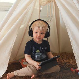 Pieni lapsi kuulokkeet korvilla tutkii tablettilaitetta.