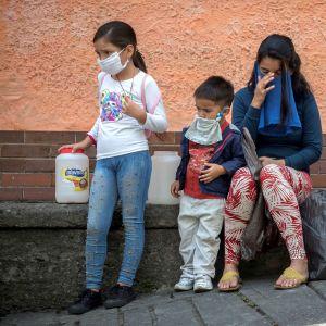 Vesipula vaikeuttaa koronaviruksen torjuntaa. Äiti jonotti vettä Caracasissa lastensa kanssa viime viikolla.