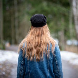 Nainen seisoo metsässä selkä päin kameraan.