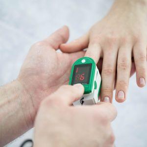 Pienellä laitteella mitataan veren happiarvoa sormen päästä.