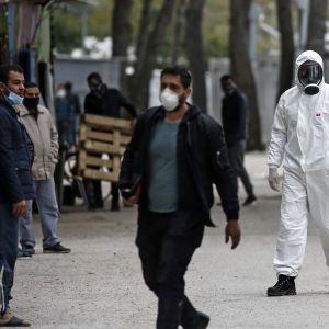 Flyktingar och flyktingarbetare vandrar på det grekiska flyktinglägret Ritsona norr om Aten. Lägret har försatts i karantän på grund av coronasmitta på lägret.
