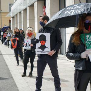 Szczecin kaupungissa kasvosuojiin pukeutuneet mielenosoittajat vastustavat lakialoitteita jonottamalla kaupan edustalla 14. huhtikuuta 2020. Jonottamalla he eivät riko koronaviruksen takia asetettua kokoontumisrajoitusta.