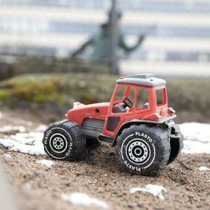 leikkitraktori hiekkalaatikolla, lapsi juoksee taustalla