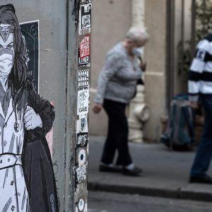 Ett äldre par i skyddsmasker går förbi en väggmålning av en läkare i skyddskläder.