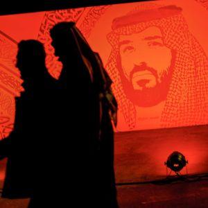 Saudier promenerar under ett porträtt av Prins Mohammad bin Salman