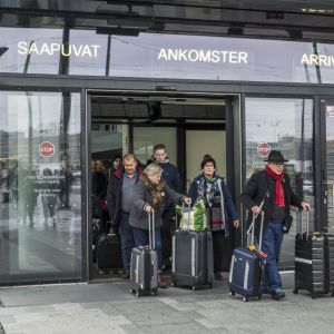 Människor med reseväskor lämnar Västra terminalen i Helsingfors.