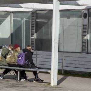 Tyttöjä ryhmässä koulun edessä
