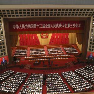 En bild av den kinesiska nationella folkkongressen fotad uppifrån. Man ser ledamöterna och en stor scen.