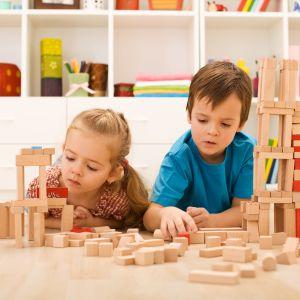 två barn leker med byggklossar på golvet
