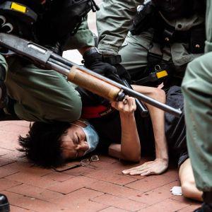 Poliser trycker ned en demonstrant mot marken. En av polisern ahåller ett gevär i handen.