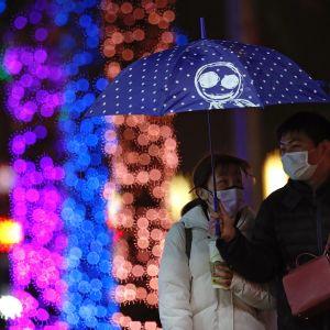 Kasvomaskeihin pukeutunut pariskunta kävelee vesisateessa sateenvarjon alla Taiwanin pääkaupungissa Taipeissa. Taustalla näkyy neonvaloja.