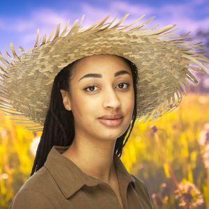 Maimouna står iklädd med sommarhatt på huvudet på en sommaräng.