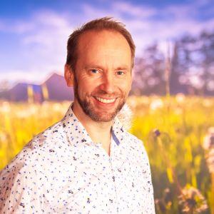 Erik-André Hvidsten ler rakt in i kameran, i bakgrunden syns en sommaräng.