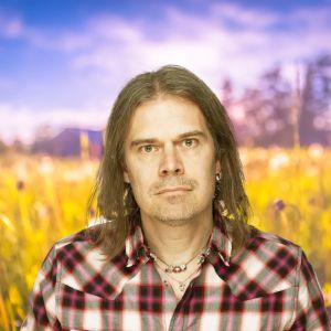 Filip Saxén ser rakt in i kameran och i bakgrunden syns en sommaräng.