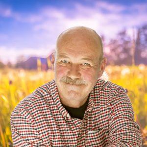 Peik Stenberg ler mot kameran med en sommaräng som syns i bakgrunden.