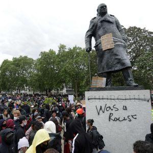 Attack mot en staty som föreställer den tidigare premiärministern Winston Churchill.  Demonstration 7.6.2020 i centrala London