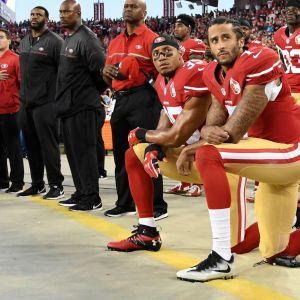 Colin Kaepernick  och Eric Reid knäböjer i protest då nationalsången spelas
