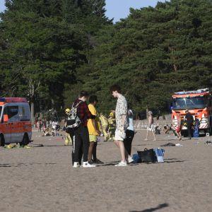 Ambulans och brandbil på stranden.